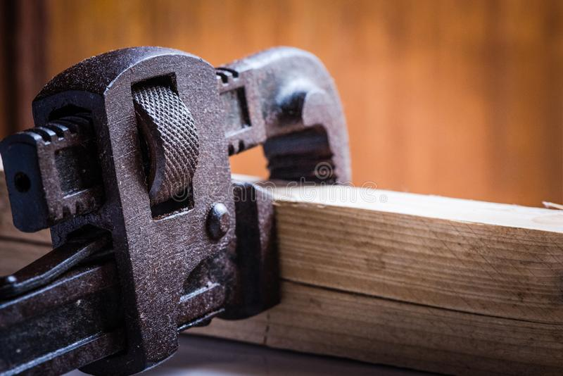 Concept shot of Stained Pipe Wrench handtool. Conept shot of stained pipe wrench hand tool calmped a wooden peice in  background stock images