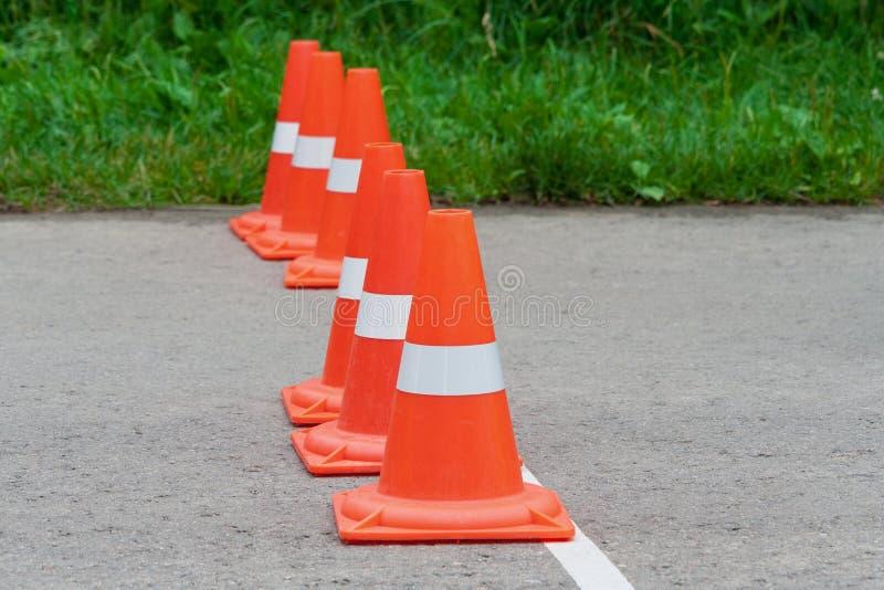Cones alaranjados do tráfego que estão em seguido imagem de stock