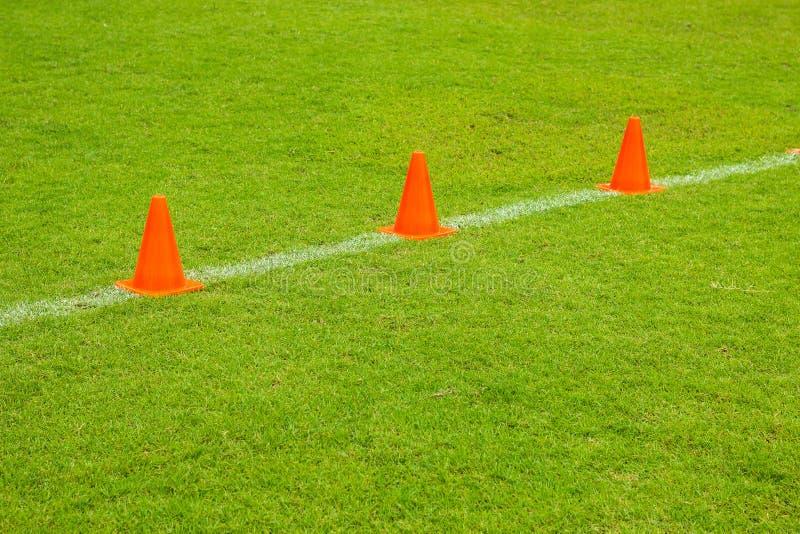 Cones alaranjados no campo do verde do futebol ou do futebol do relvado, equipamento de treino fotos de stock royalty free