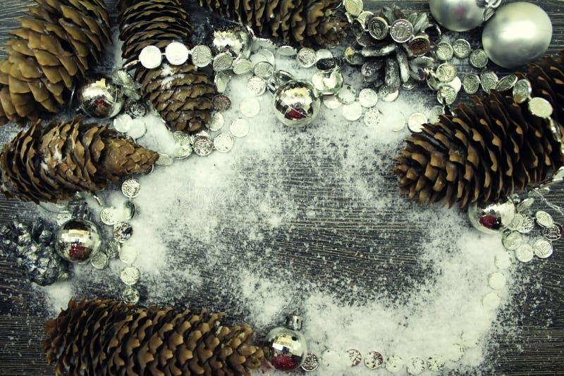 Cones de abeto e decorações do Natal na neve no fundo de madeira fotografia de stock royalty free