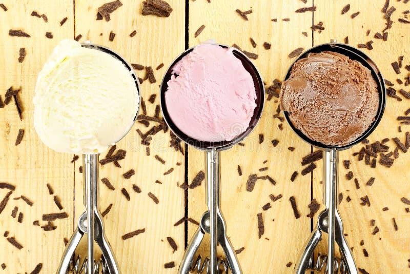Cones de gelado da morango, do chocolate, da baunilha e do pistachio sobre o fundo branco foto de stock