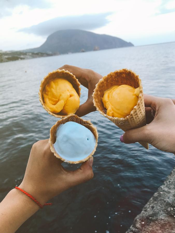 Cones de gelado nas mãos fêmeas contra o fundo do mar imagem de stock royalty free