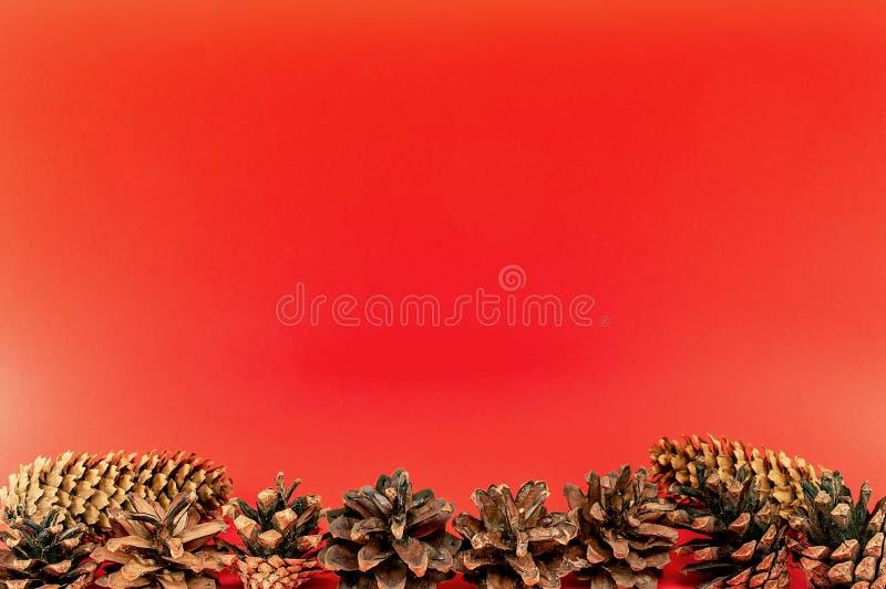 Cones do abeto vermelho e do pinho em um ano novo do Natal vermelho da celebração do cartão do fundo imagem de stock