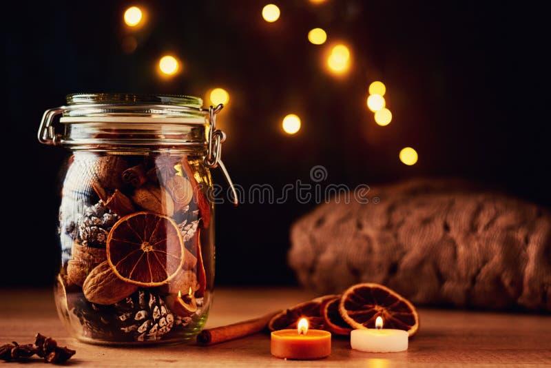 Cones do pinho no frasco de vidro e em luzes feericamente em um fundo escuro Decorações festivas imagens de stock royalty free