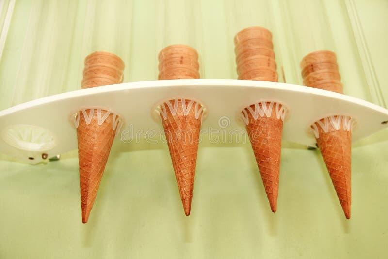 Cones do waffle do gelado no distribuidor Os cartuchos do gelado embalaram no distribuidor na parede da loja Loja de pastelaria i fotos de stock royalty free