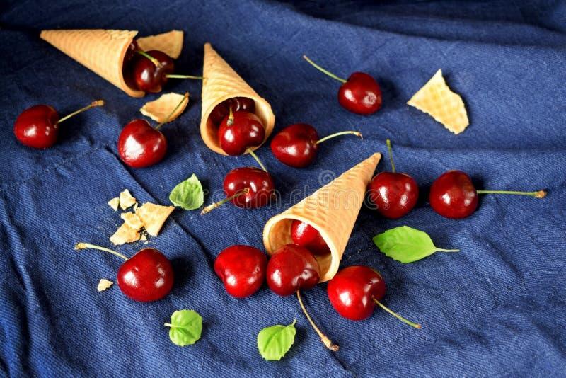 Cones e cerejas do waffle no fundo azul foto de stock royalty free