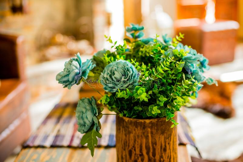 Cones of green hops. Artificial silk flowers in interior.Still life with bouquet in a ceramic, wooden vase on wooden. Cones of green hops. Artificial silk royalty free stock photos