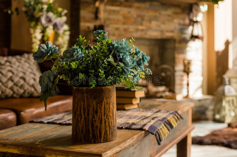Cones of green hops. Artificial silk flowers in interior.Still life with bouquet in a ceramic, wooden vase on wooden. Cones of green hops. Artificial silk stock image