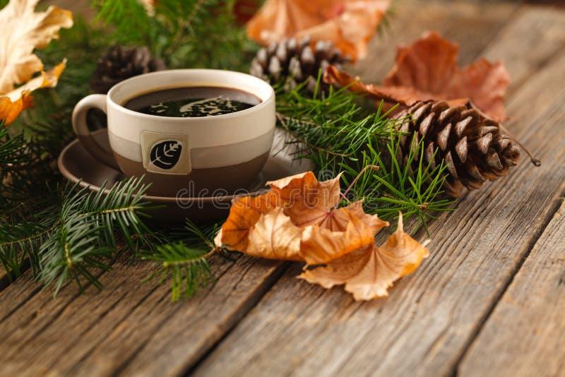 Coneson chaud de café et de pin sur le fond en bois de table avec la copie s photographie stock libre de droits