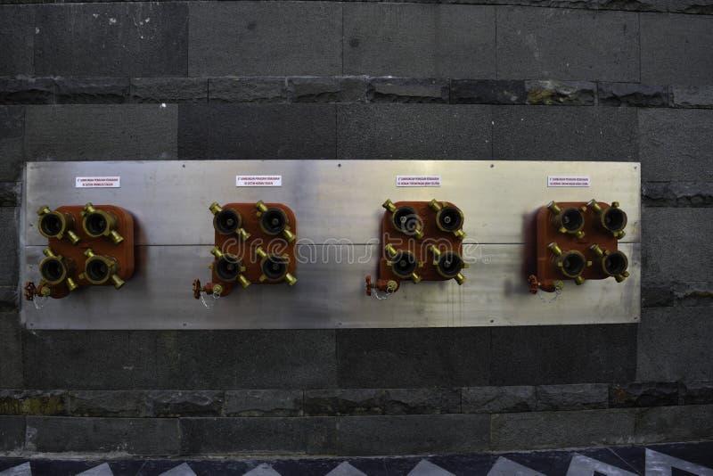 conexão do extintor ao sistema de sistema de extinção de incêndios da estação no fundo da parede fotos de stock royalty free