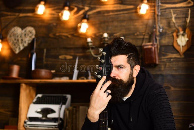 Conex?o com a m?sica O m?sico farpado do homem aprecia nivelar com guitarra-baixo, fundo de madeira Homem com abraços da barba fotos de stock royalty free