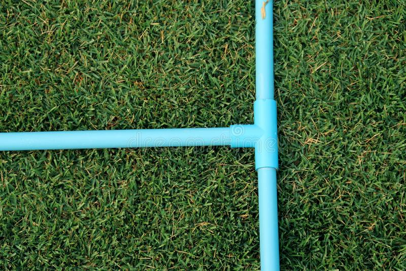 Conexión de tubo, tubo del PVC del zócalo de T, tubo azul del pvc de la manera del árbol en jardín verde fotografía de archivo
