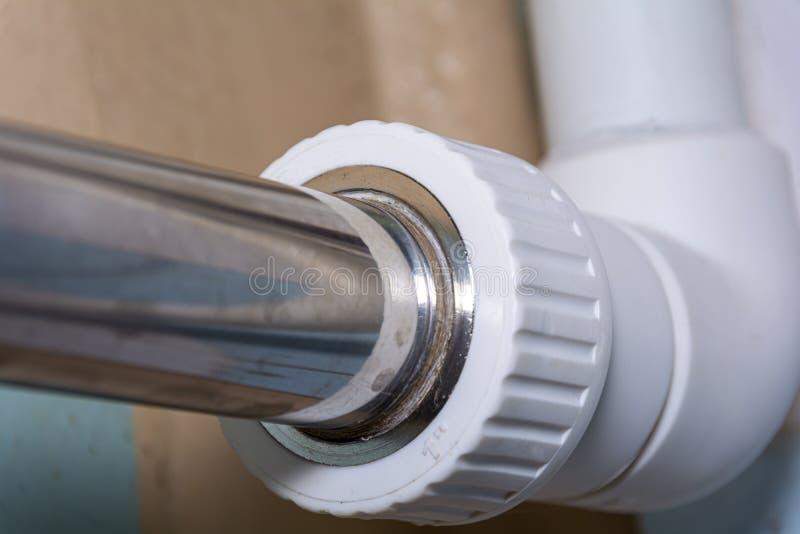 Conexión de una tubería metálica a una tubería de PVC. Cierre. Concepto: suministro y fontanería de agua, mantenimiento y rep foto de archivo