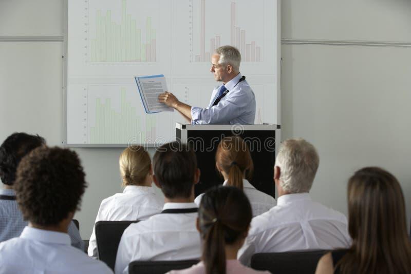 Conférence de Delivering Presentation At d'homme d'affaires âgée par milieu photographie stock libre de droits