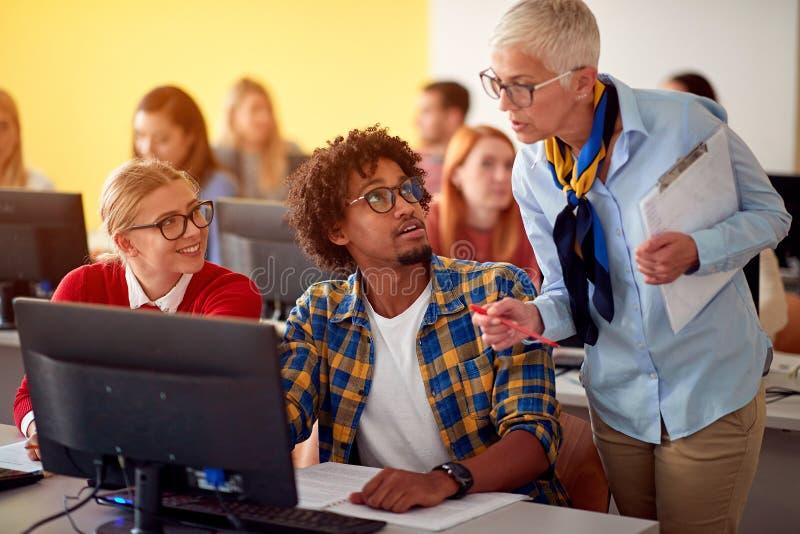 Conférencier dans la classe d'ordinateur aidant l'étudiant sur l'université images libres de droits