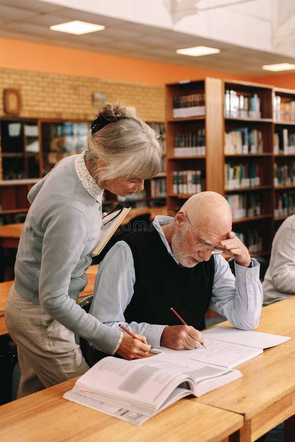 Conférencier supérieur aidant un homme plus âgé dans la classe d'université photo stock