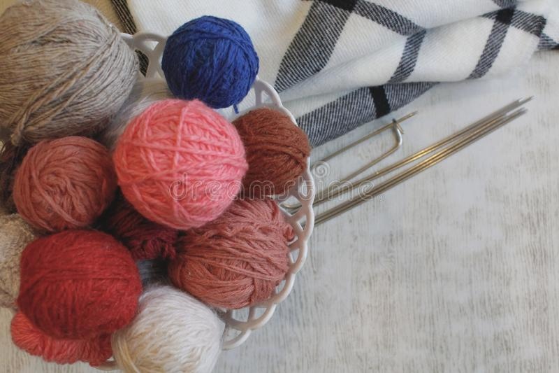 Confecção de malhas, conforto, bordado Bolas coloridas do fio em uma cesta, agulhas de confecção de malhas Copyspace fotos de stock royalty free