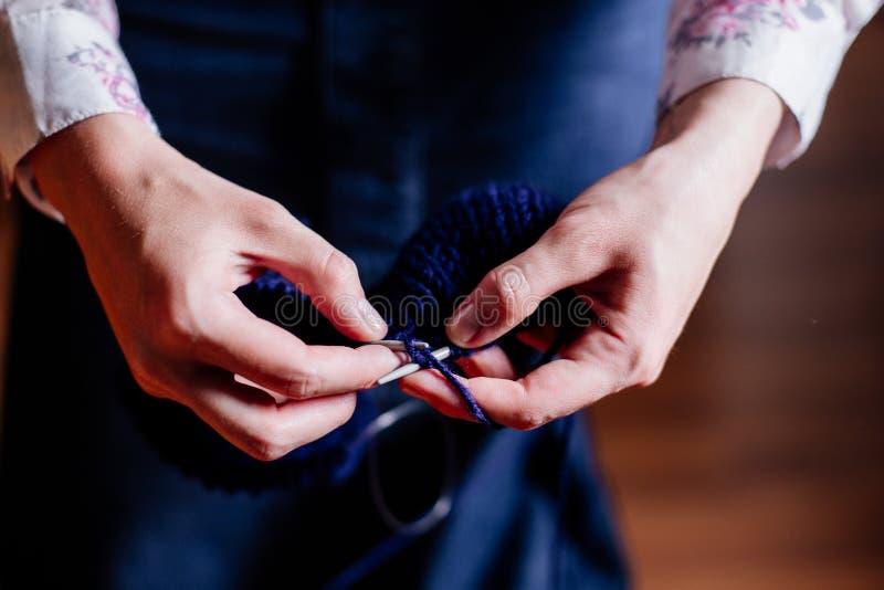 Confecção de malhas pelas mãos do ` s das mulheres imagens de stock