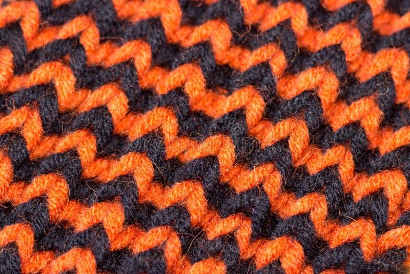 Confecção de malhas Textura feita malha fundo Agulhas de confecção de malhas brilhantes Fio de lãs alaranjado e preto para fazer  imagens de stock royalty free