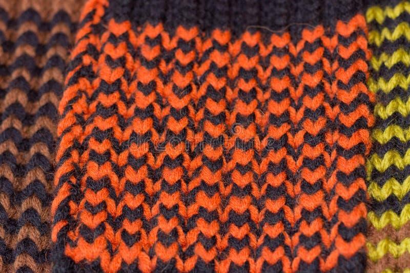 Confecção de malhas Textura feita malha fundo Agulhas de confecção de malhas brilhantes Fio de lãs alaranjado e preto para fazer  foto de stock