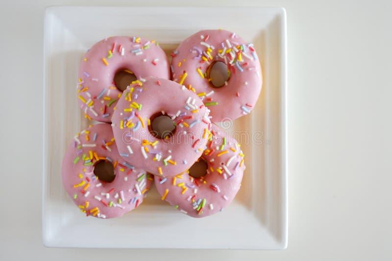 Confection 5 сладостный розовый донутов, который служат на квадратной белизне Pl стоковые фото