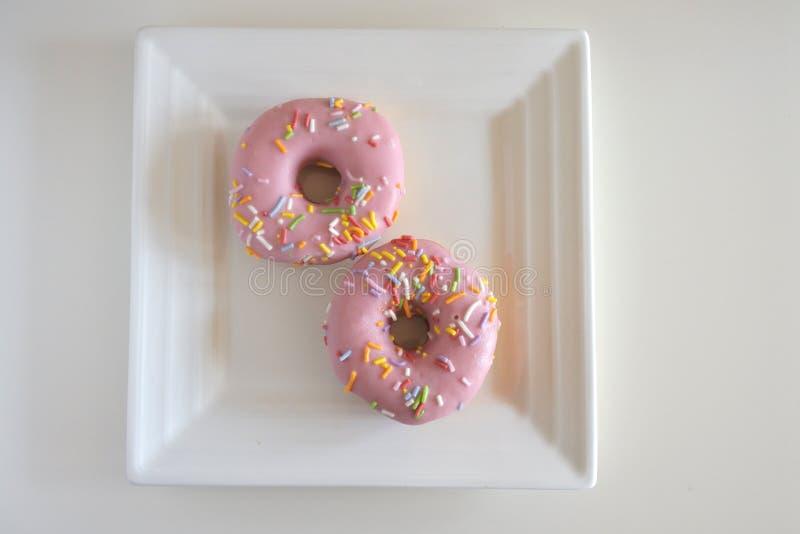 Confection 2 сладостный розовый донутов, который служат на квадратном Pla белизны стоковое изображение