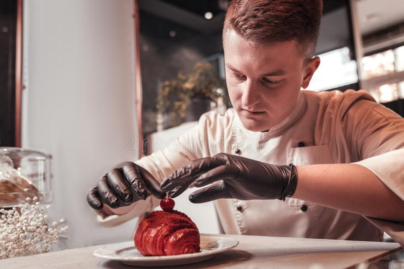 Confectioner accurately decorating the dessert with a cherry. The last detail. The concentrated confectioner accurately decorating the dessert with a cherry royalty free stock photography
