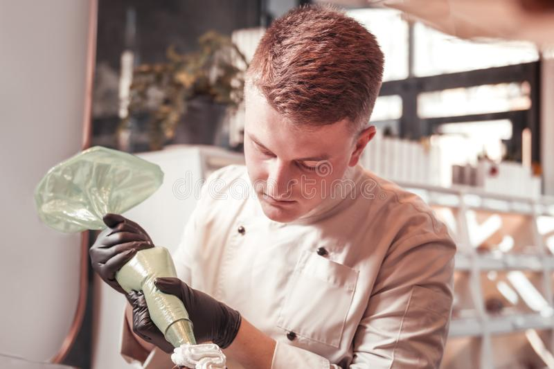 Confectioner accurately working with a cream bag stock photo