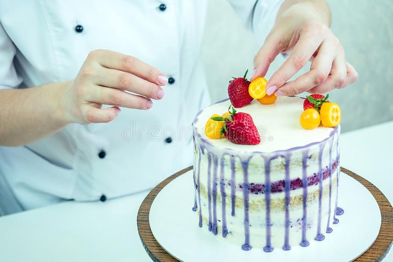 Confectioner in black gloves and white work uniform adorns the cake in the kitchen. confectioner, cake, cooking. wedding. And birthday cake with berries royalty free stock photos
