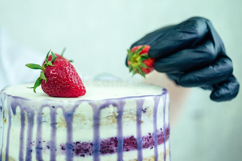 Confectioner in black gloves and white work uniform adorns the cake in the kitchen. confectioner, cake, cooking. wedding. And birthday cake with berries royalty free stock image