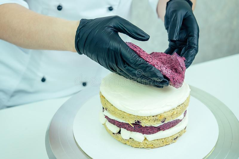 Confectioner in black gloves and white work uniforms puts cream on the cake on the table. confectioner, cake, cooking. Confectioner in black gloves and white royalty free stock images