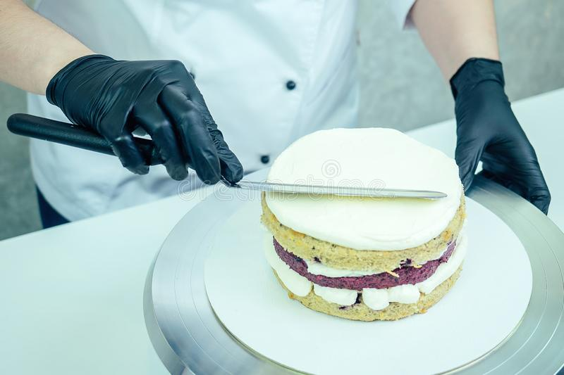 Confectioner in black gloves and white work uniforms puts cream on the cake on the table. confectioner, cake, cooking. Confectioner in black gloves and white stock photography
