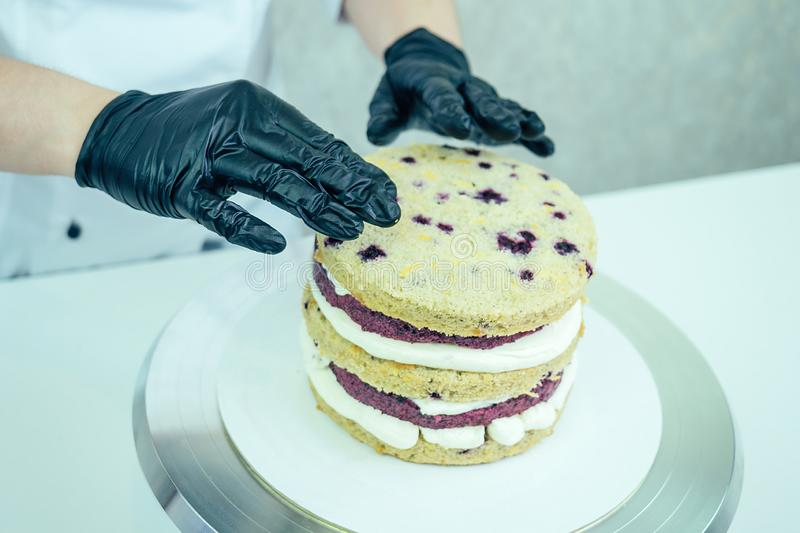 Confectioner in black gloves and white work uniforms puts cream on the cake on the table. confectioner, cake, cooking. Confectioner in black gloves and white royalty free stock photo