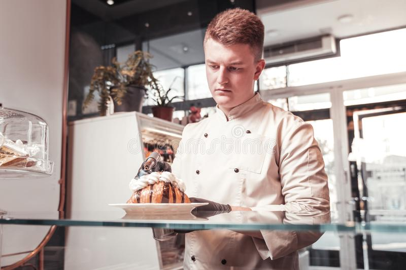 Confectioner caramelizing his dessert using special equipment royalty free stock photos