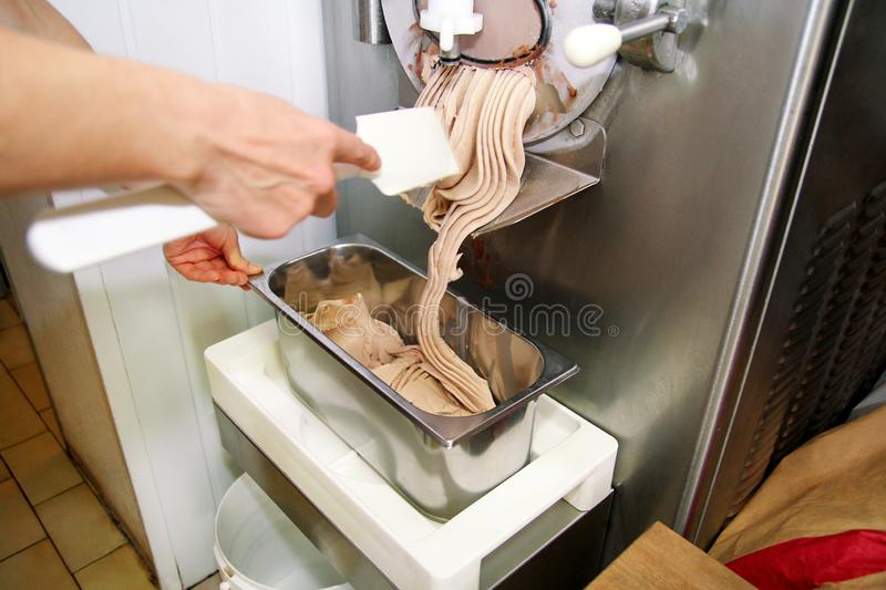 Confectioner in chef uniform is working on ice cream maker machine. Woman is producing ice cream of hazelnut flavors. royalty free stock photos