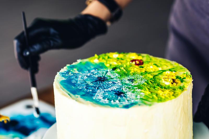 Confectioner decorate cake with colorful cream. handmade cake with pattern royalty free stock image