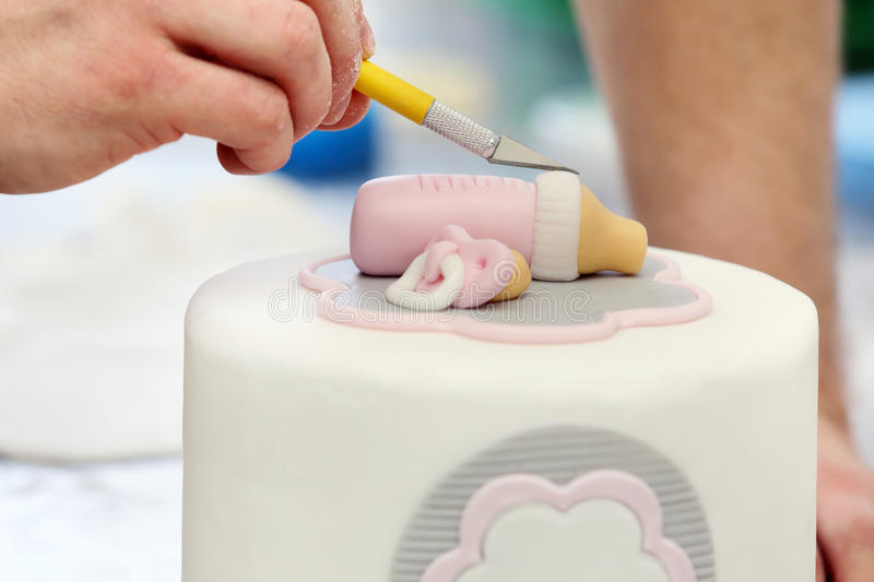 Confectioner decorates birthday cake in bakery royalty free stock photo