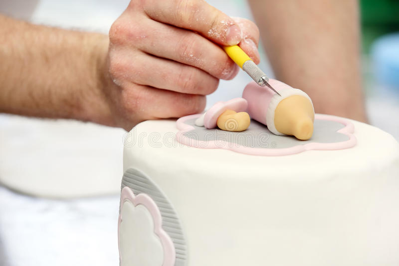 Confectioner decorates birthday cake in bakery royalty free stock photos