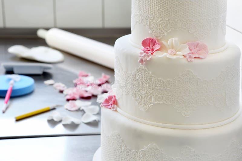 Confectioner decorates wedding cake in bakery stock image