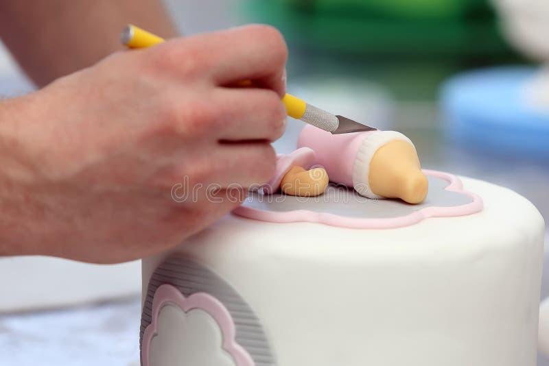 Confectioner decorates white birthday cake stock photo