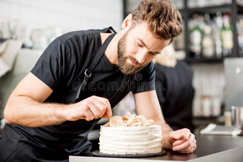 Confectioner decorating a pie. Handsome confectioner in black t-shirt decorating a pie at the bar of the modern cafe interior royalty free stock photo