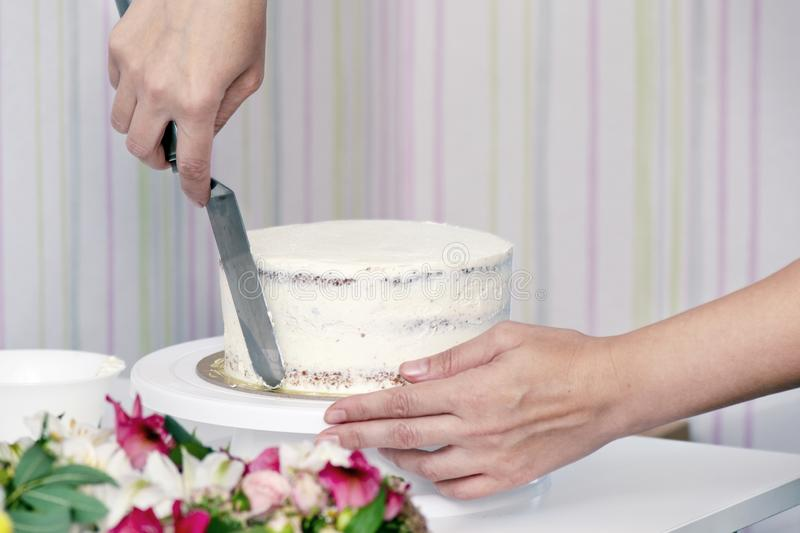 The confectioner`s hands decorate the cake with white cream stock photography