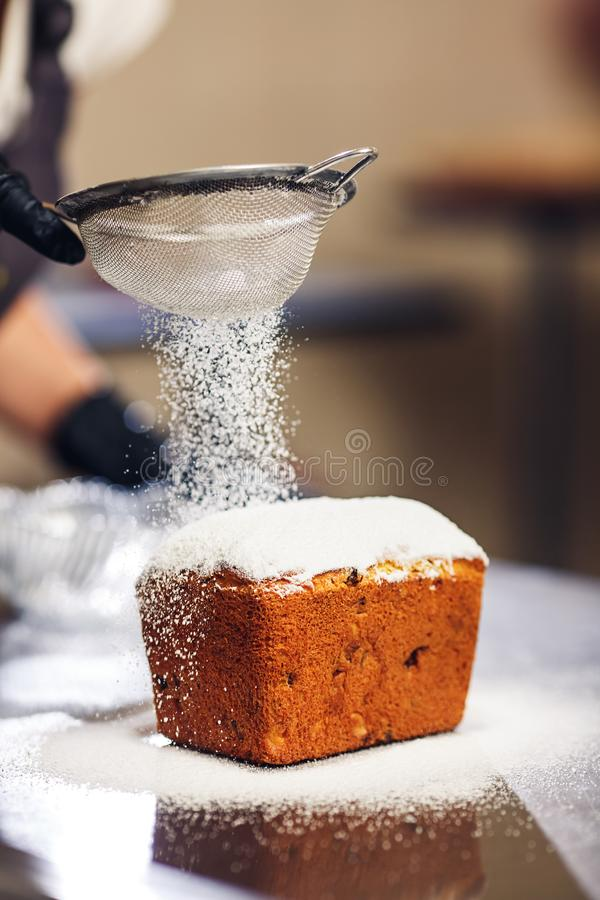 Confectioner sprinkles Easter cake with icing sugar through sieve.  royalty free stock photo