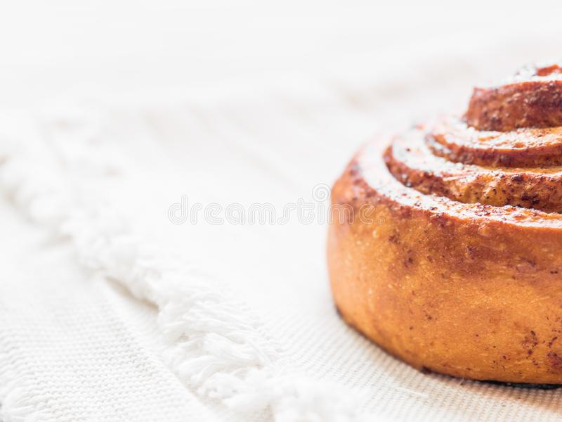 Confectionery baking. Sweet fresh soft roll bun with cinnamon on white background. Cinnabon closeup.  royalty free stock photo