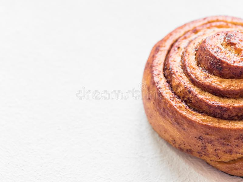 Confectionery baking. Sweet fresh soft roll bun with cinnamon on white background. Cinnabon closeup.  royalty free stock photography