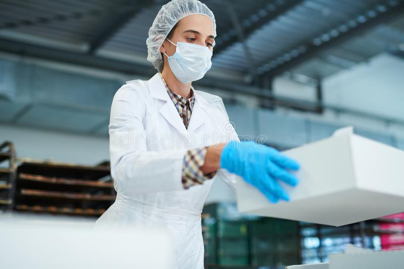 Confectionery factory worker holding paper box royalty free stock photos