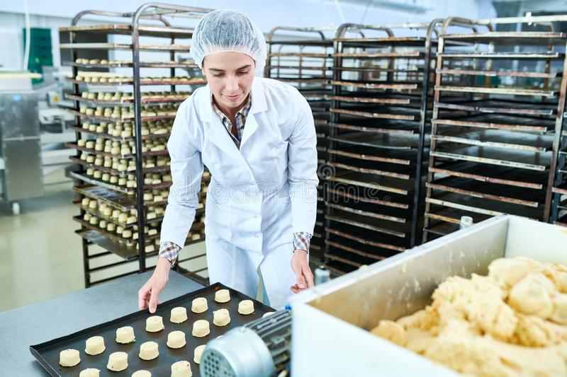 Confectionery factory worker holding tray with uncooked pastry. Confectionery factory employee in white coat standing and holding baking sheet with raw pastry royalty free stock photo