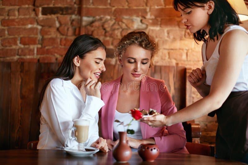 confectionery Mulheres que provam doces de chocolate no café imagem de stock
