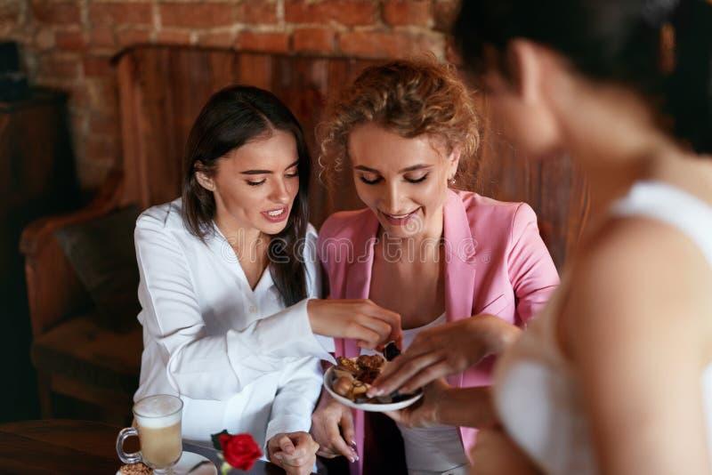 confectionery Mulheres que provam doces de chocolate no café foto de stock