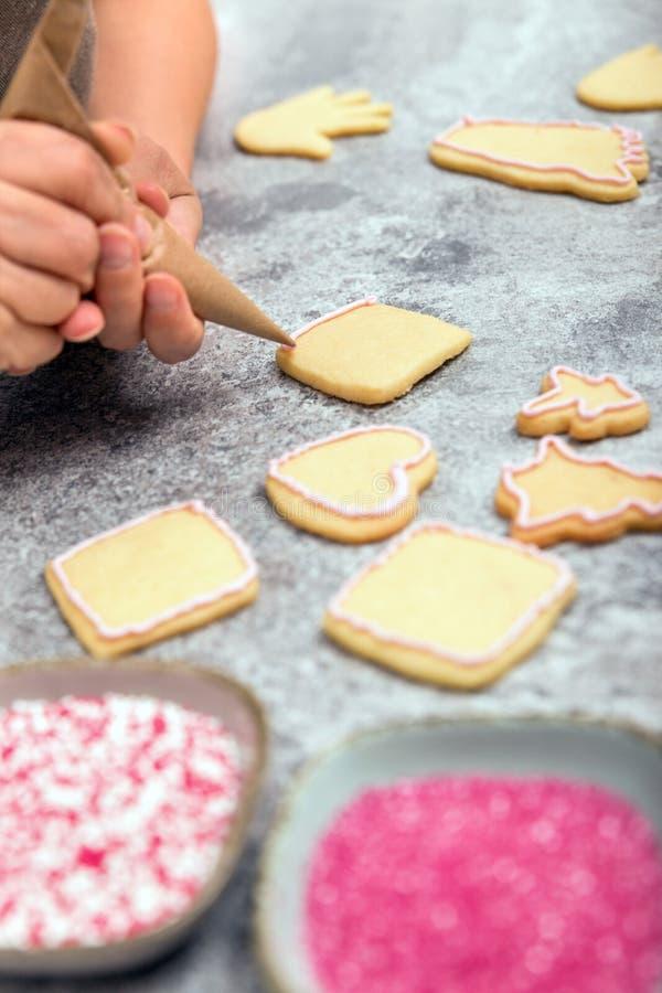Confectionist est des biscuits de Noël de décoration avec le glaçage, frosti images libres de droits